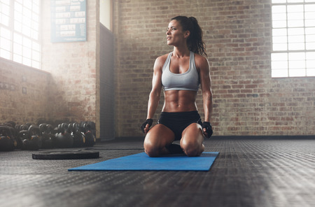 ジムで運動筋肉の若い女性の屋内撮影。スポーツ ウエア エクササイズ マットの上に座って、よそ見でフィットネス モデル。