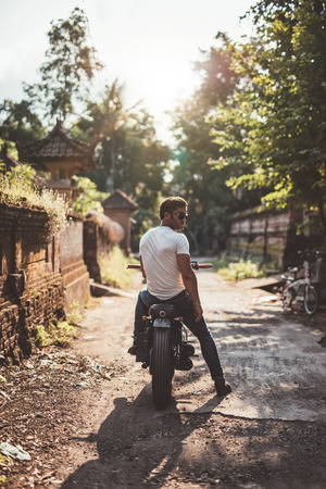 village man: Outdoor shot of young man sitting on his motorcycle. Young male riding motorbike through a village.