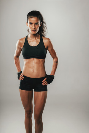 Strong fit young woman in black sportswear posing with her hands on her hips looking confidently at the camera over grey with copy space