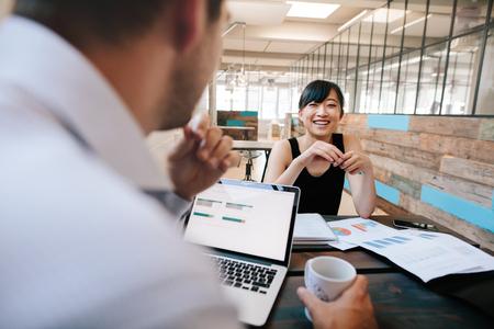 사무실에서 작업을 논의 두 사업 동료의 총입니다. 사무실 매니저와 젊은 아시아 여자 회의 미소.