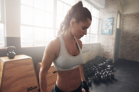healthy looking: Portrait of healthy young woman in sportswear standing in the gym. Fitness female in sportsbra looking down.