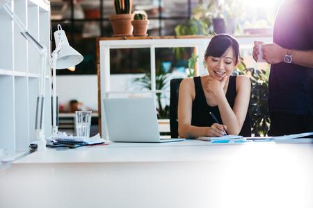 Shot von lächelnden asiatischen geschäftsfrau schriftlich Notizen auf Notizblock mit Kollegen stehend von. Weibliche Führungskraft arbeitet an ihrem Schreibtisch mit Laptop Notizen. Standard-Bild