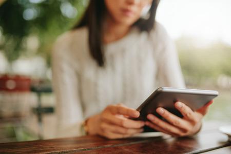 카페 테이블에 앉아 젊은 여성 쐈어. 커피가 게에서 태블릿을 사용하는 여자. 디지털 태블릿에 중점을 둡니다.