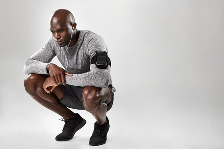 Young african male model with armband and earphone crouching and looking down thinking on grey background with copy space.