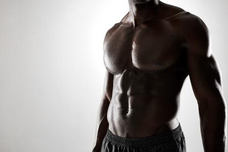 modelos hombres: Cierre de tiro de hombre joven africana con cuerpo musculoso contra el fondo gris. Modelo masculino descamisado con abs muscular. Foto de archivo