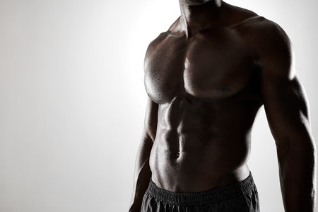 Close up shot of young african man with muscular body against grey background. Shirtless male model with muscular abs.