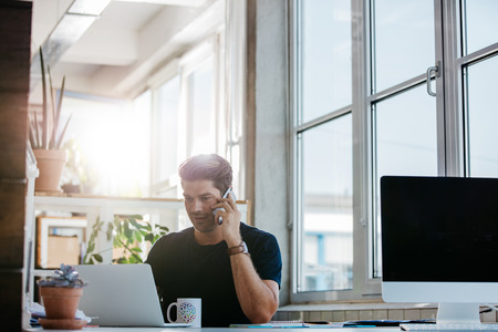 business man phone: Shot of confident young man sitting at his office using laptop and talking on mobile phone. Business man working at his desk. Stock Photo