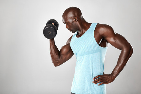 flexing: Shot of young muscular man doing heavy dumbbell exercise for biceps. African fitness model working out with dumbbells on grey background.