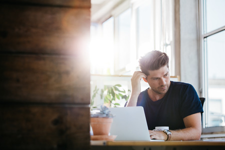 business problems: Young business man with problems and stress in the office. Man at his desk with laptop and looking away thinking. Stock Photo