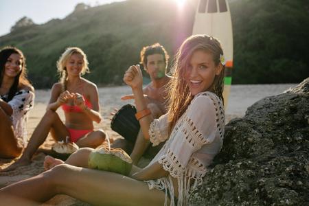 백그라운드에서 그녀의 친구와 함께 해변에서 재미 흥분된 젊은 여자. 여름 휴가 해변에서 즐기는 친구의 그룹.