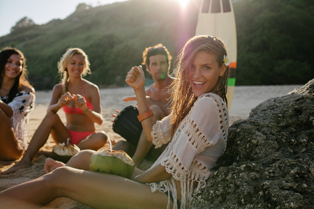 Aufgeregte junge Frau, die Spaß mit ihren Freunden im Hintergrund am Strand. Gruppe von Freunden Sommerferien am Strand zu verbringen.