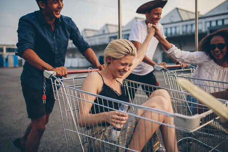 Young friends having fun on a shopping carts. Multiethnic young people playing with shopping cart. Stock Photo