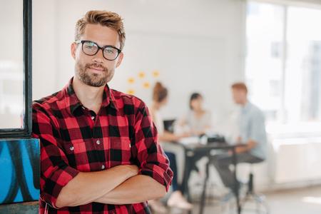 Retrato de un pie mirando joven profesional de negocios positivo con los brazos cruzados con compañeros de trabajo hablando en segundo plano.