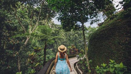 tropical garden: Rear view shot of young woman in hat walking in tropical garden. Female tourist enjoying a day in nature.