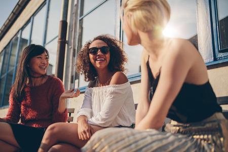 Drie jonge vrouwen die bij openlucht en koffie samenkomen die kletsen genieten van. Groep vrouwelijke vrienden die pret hebben terwijl het zitten in een terras.