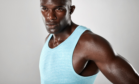 muscular build: Close up shot of confident young african man with muscular build looking away over grey background. Stock Photo