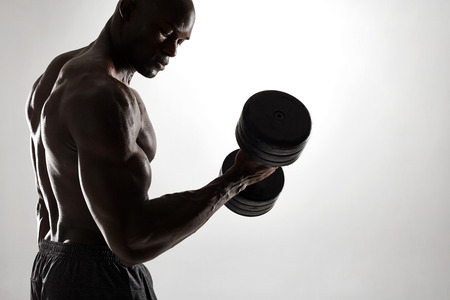 man working out: Silhouette of healthy muscular young man working out with dumbbells against grey background. Bodybuilder exercising with heavy weights. Stock Photo
