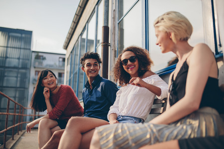 sitting people: Shot of multiethnic group of friends sitting in balcony and talking. Young people relaxing outdoors in terrace and smiling. Stock Photo