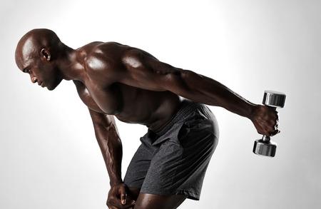 Zijaanzicht van de jonge Afrikaanse mens wordt geschoten die met domoren tegen grijze achtergrond uitwerken die. Gespierde man shirtless oefenen met zware gewichten.