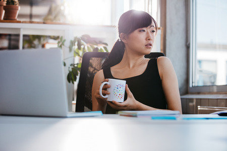 Portrait der entspannten jungen Frau sitzt an ihrem Schreibtisch mit Tasse Kaffee und Wegschauen. Asiatische Geschäftsfrau, die Kaffeepause im Büro nimmt.