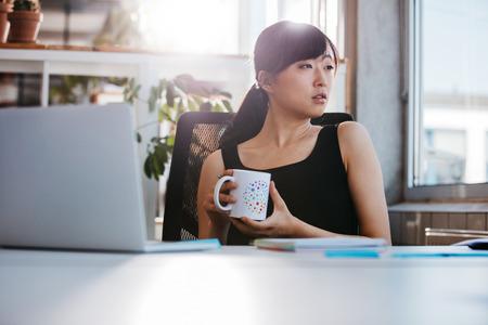oficina: Retrato de mujer joven relajado sentado en su escritorio sosteniendo taza de café y mirando a otro lado. Mujer de negocios asiática tomando descanso para el café en la oficina.