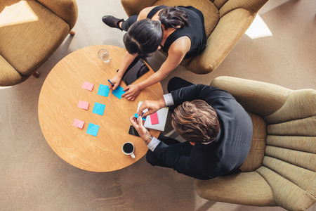 Top view of businessman and businesswoman discussing over adhesive notes on table in office lobby. Businesspeople preparing notes.