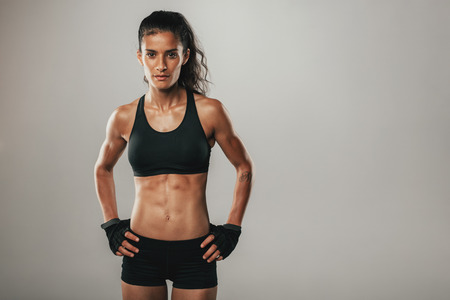 hands on hips: Fit healthy young woman with a toned physique standing looking seriously at the camera with her hands on her hips over grey with copy space