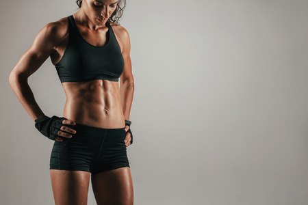 Attractive muscular woman with gloved hands on hips showing off her strong abs over gray background Stock Photo