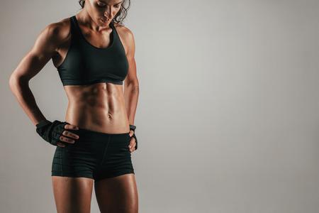 muscle training: Attraktive muskulösen Frau mit behandschuhten Händen auf den Hüften ihre starke abs über grauem Hintergrund vorführt