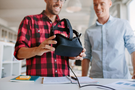 experiments: Shot of two men using virtual reality goggles in office. Business partners working in office, standing at a table with VR glasses. Stock Photo