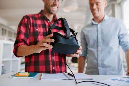 Tiro de dos hombres que usan gafas de realidad virtual en el cargo. Los socios comerciales de trabajo en la oficina, de pie en una mesa con gafas de realidad virtual. Foto de archivo