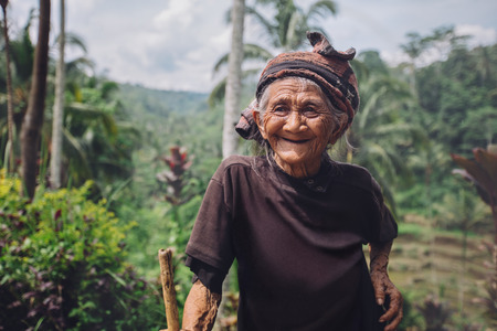 wrinkled: Portrait of happy senior woman with a cane in village. Smiling old female outdoors in countryside. Stock Photo