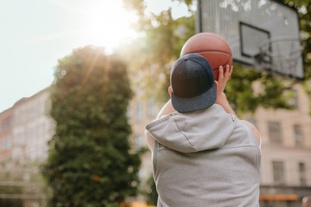 Rear view shot of a streetball player shoots basketball. Young guy playing basketball on outdoor court on a summer day.