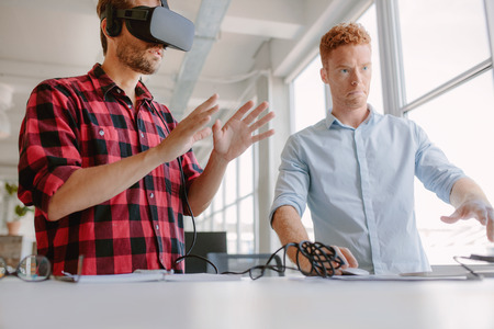 uses a computer: Developers testing an augmented reality device with a broad range of uses from gaming to visual aid. Young man wearing vr headset with coworker working on computer.