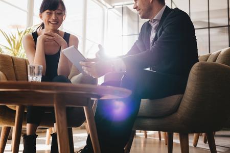 デジタル タブレットを使用してビジネスのアイデアを議論する 2 つの企業の同僚。オフィスのロビーで女性パートナーと会議を持つ青年実業家 写真素材