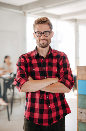 Portrait of happy young startup owner standing in office with coworkers meeting in background.