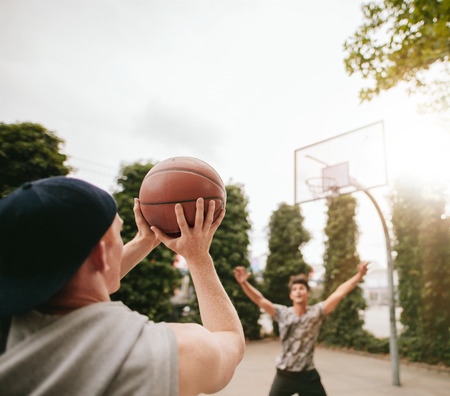 blocking: Young man shoots the ball to the basket with friend in background blocking. Friends playing basketball against each other on outdoor court.