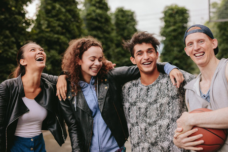 four people: Portrait of four young friends smiling together. Mixed race group of people enjoying outdoors.