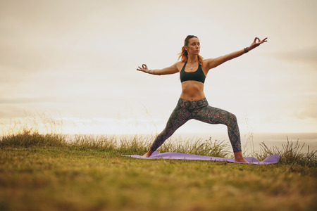 Shot of fit young woman doing yoga on cliff. Healthy female practicing yoga pose outdoors. Stock Photo
