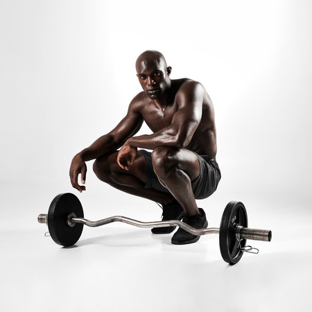 masculine: Portrait of a muscular man crouching with barbell over grey background. African fitness model with masculine physique. Stock Photo