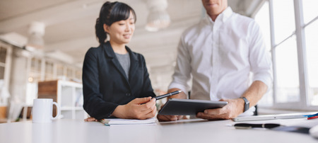 Photo de jeunes gens d'affaires utilisant une tablette numérique au travail. Deux jeunes gens à l'aide d'un ordinateur à écran tactile au bureau moderne.