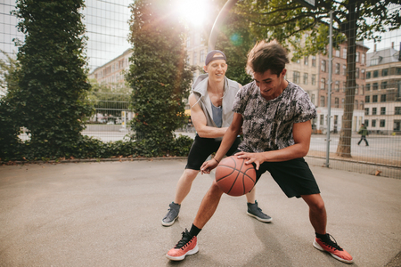 dribbling: Two young man on basketball court dribbling with ball. Friends playing basketball on court and having fun.