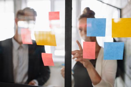 두 사업 동료 함께 프로젝트 작업. 사무실에서 유리 벽에 남성 동료에 게 스티커 메모를 가르키는 비즈니스 여자.