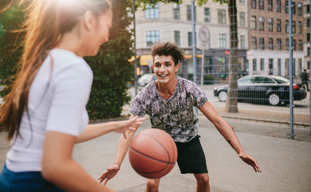 Two young man and woman playing  basketball on outdoor court. Friends having a game of basketball. Stock Photo