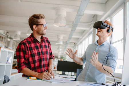 empresarial: Hombre joven que prueba la tecnología de la realidad virtual con el colega en oficina. Colegas que trabajan en mejorar la experiencia de la tecnología de auriculares VR. Foto de archivo