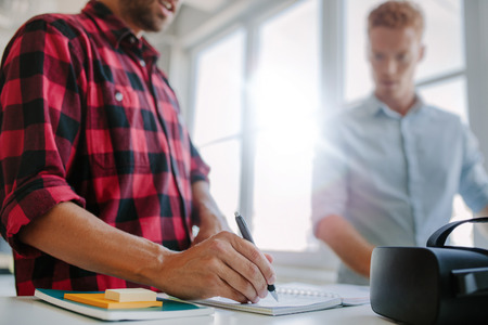 developers: Closeup shot of young man writing on notepad, with colleague standing in background. Two young developers working together in office. Stock Photo