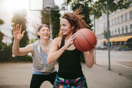blocking: Young girl playing basketball with boy blocking. Teenage friends enjoying a game of streetball on outdoor court. Stock Photo