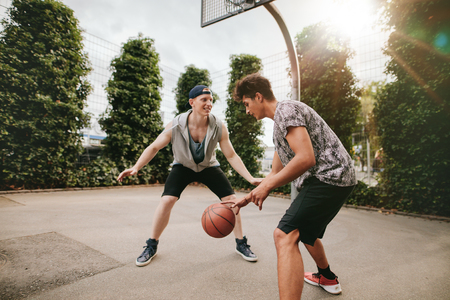 blocking: Teenagers playing basketball on outdoor court and having fun. Young man dribbling basketball with friend blocking.