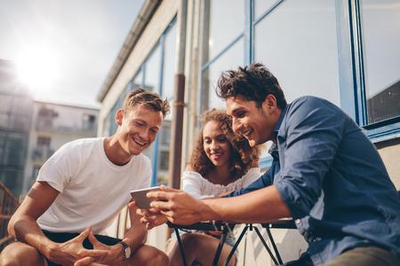 Drie jonge vrienden buiten zitten en kijken naar mobiele telefoon. Groep mensen die bij openluchtkoffie zitten en op video op smartphone letten. Stockfoto