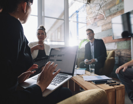 strategy meeting: Business woman with laptop discussing business strategy with colleagues. Businesspeople having a meeting. Stock Photo